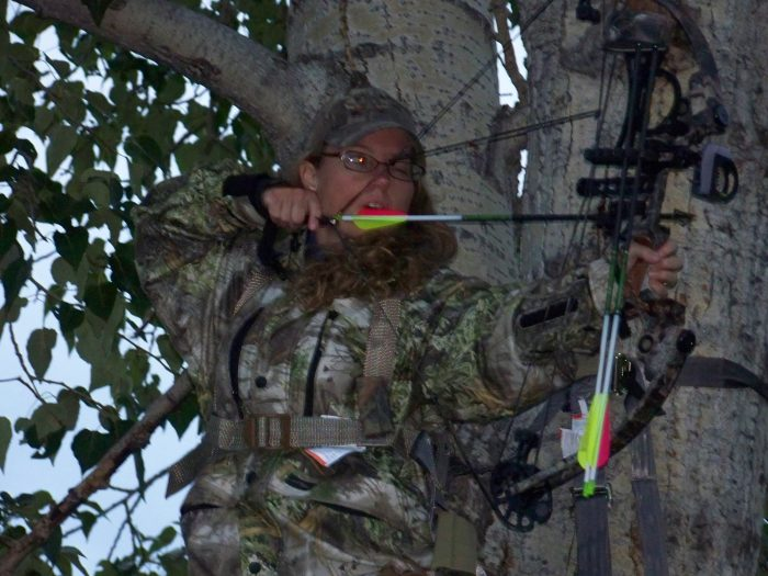 Bow hunter in tree at full draw photo cred Trigger