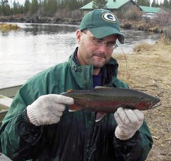 Lohrenz of Fish, Wildlife and Parks holds up a trout caught in a weir on the Madison River last fall. The fish are measured, classified as to age and sex, tagged and released. Anglers catching the tagged fish are asked to report them to FWP.